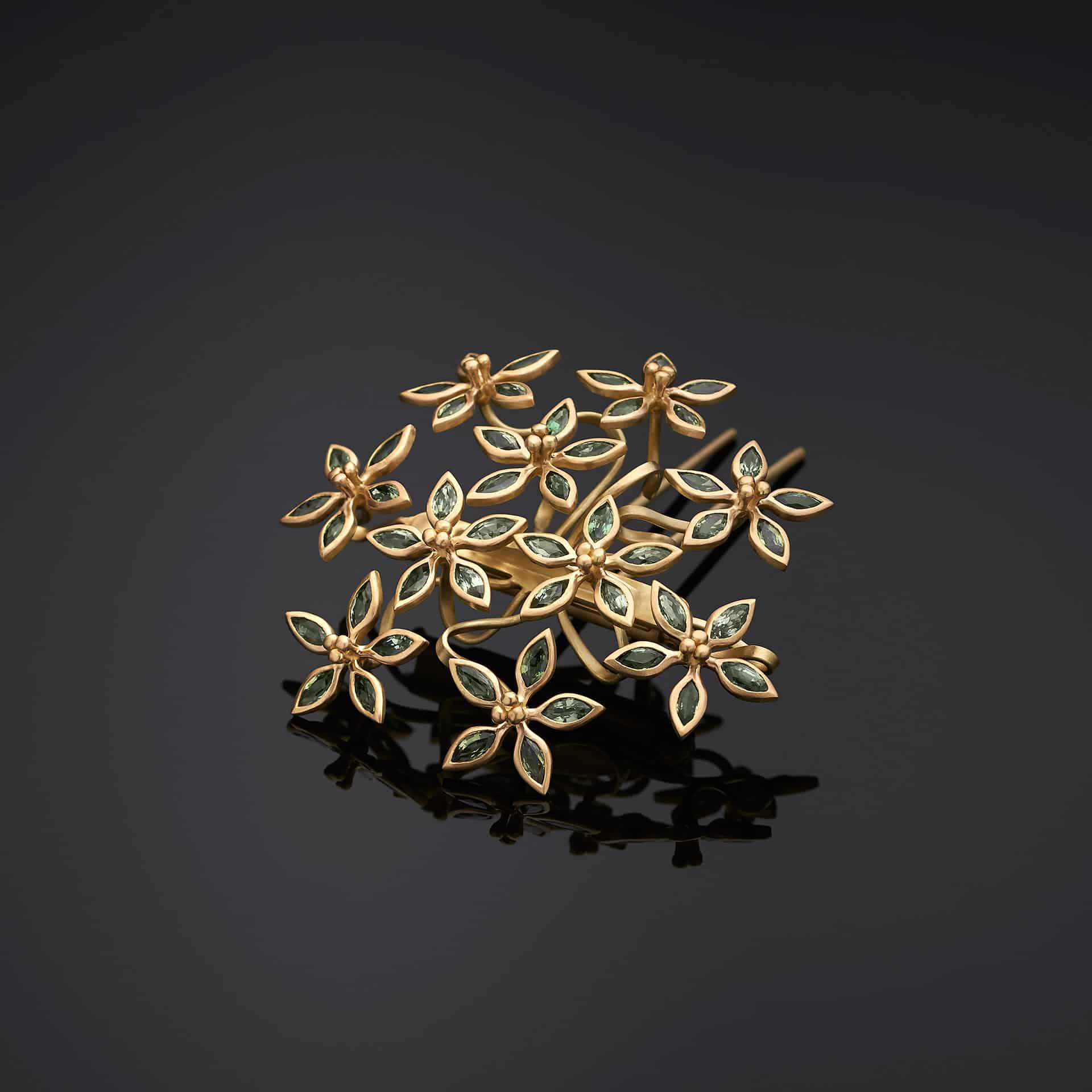 Modular hairpin-brooch in 18k gold set with 50 green sapphires